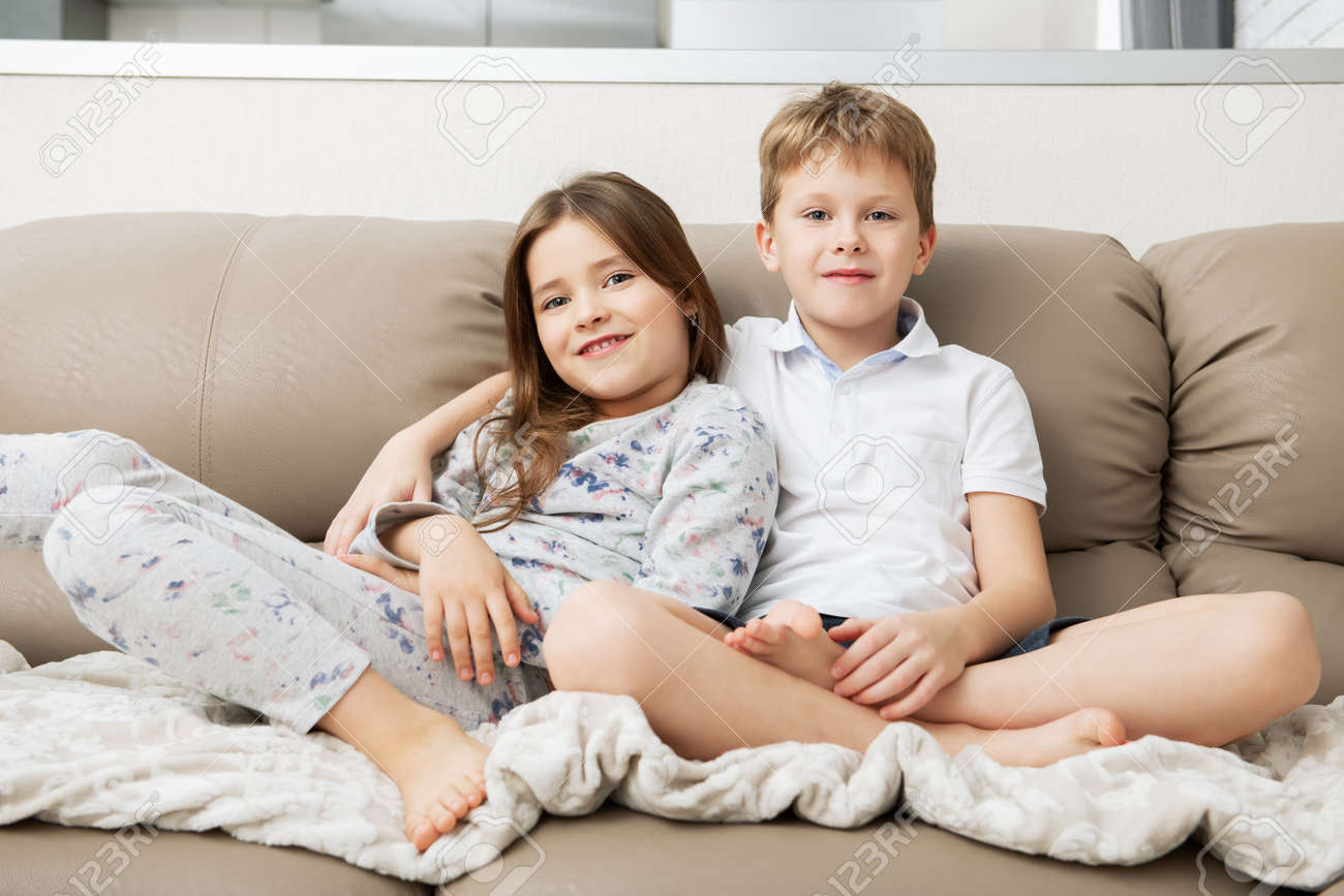 Cute boy and girl are sitting on the couch. Fashion home shot. Childhood. Kid's fashion. - 118168413