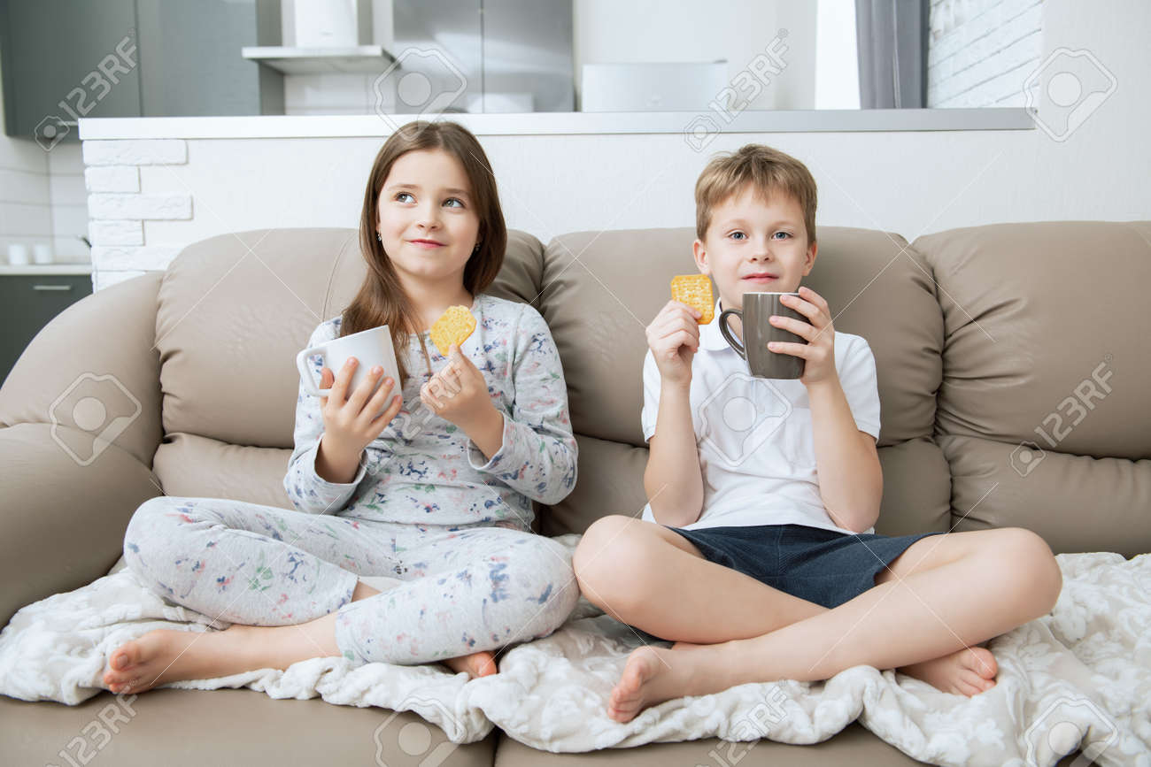 Cute boy and girl are sitting on the couch with cups. Fashion home shot. Childhood. Kid's fashion. - 118168562