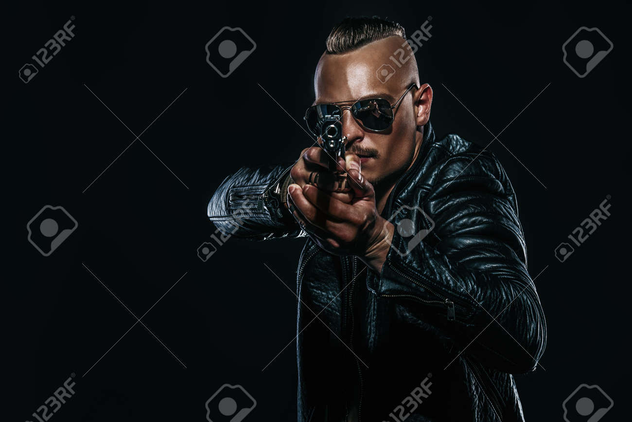 Dark portrait of a serious gangster man with gun wearing black leather jacket. - 120050426