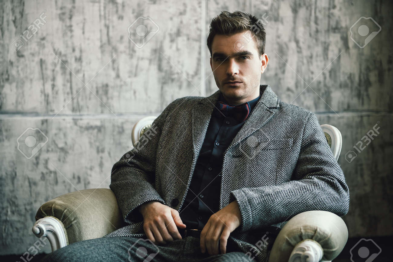 A portrait of a fashionable young man posing in the armchair over the grey background. Formal fashion for men. - 120873004
