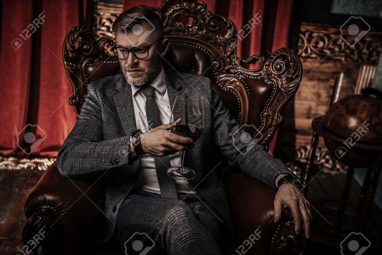 A portrait of a handsome mature man in a formal costume drinking wine in the armchair in the classic interior. Men's beauty, fashion. - 122587412