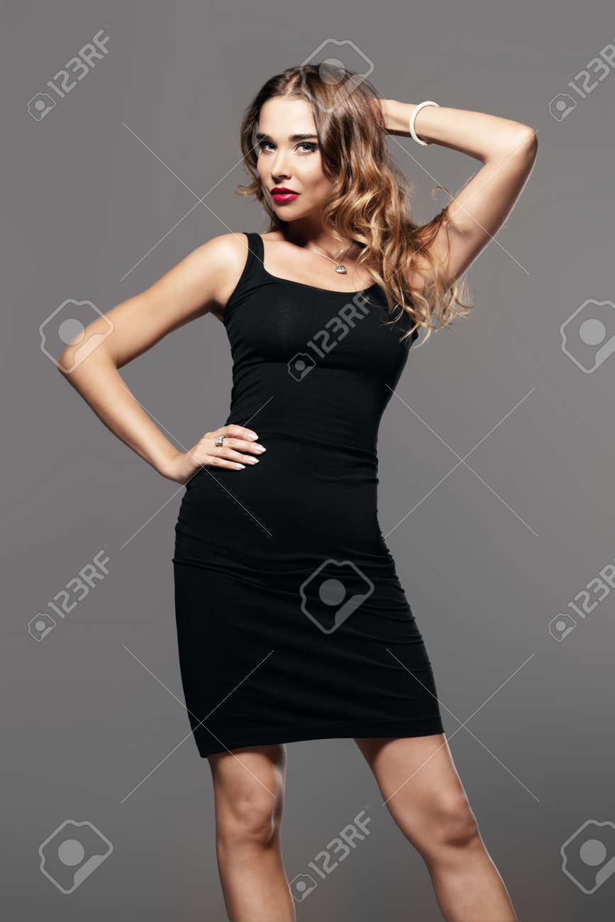 Amazing woman wearing elegant black dress and sunglasses on grey background. Beauty, fashion concept. Evening dresses collection. - 123114241