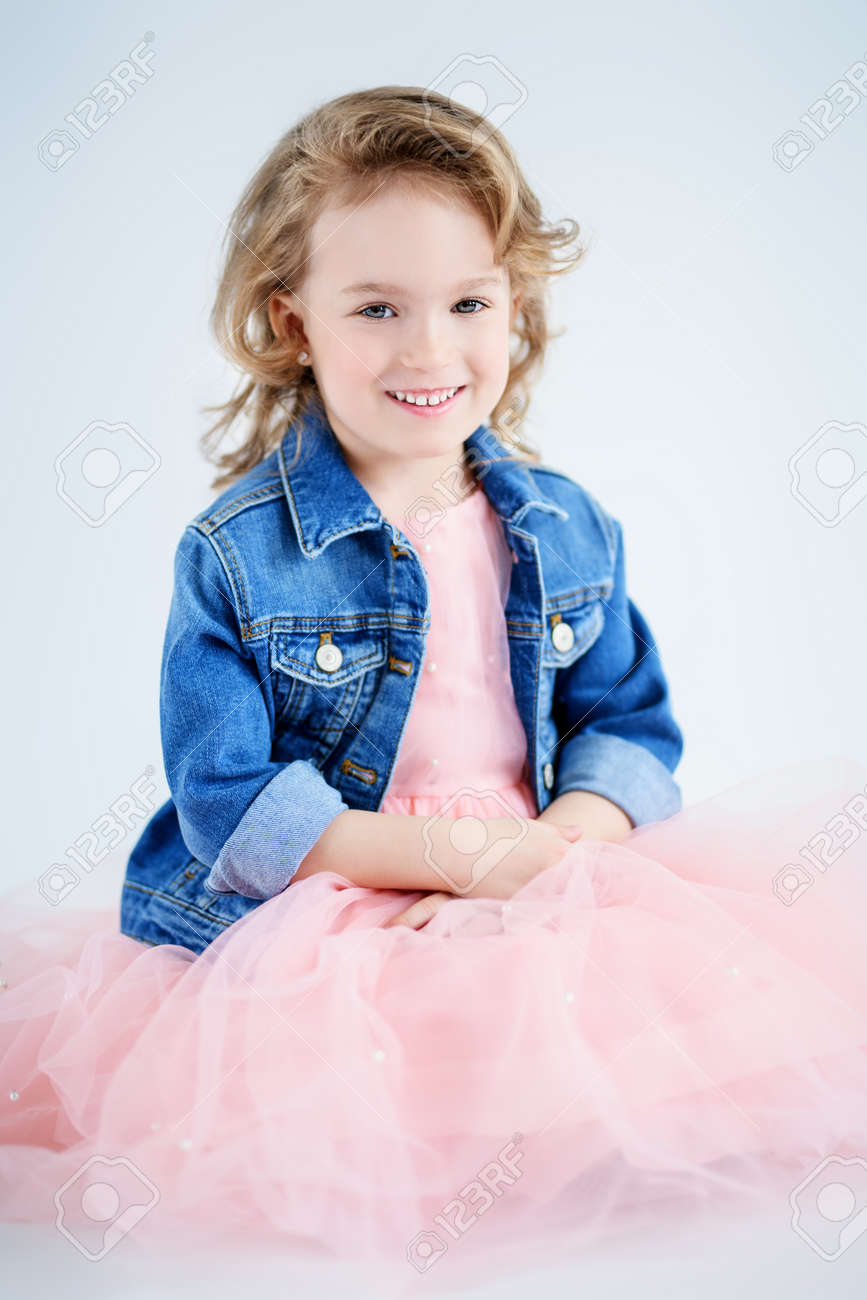 A portrait of a pretty girl in a pink dress and a denim jacket posing in the studio over the white background. Kids, fashion, beauty. - 124093180