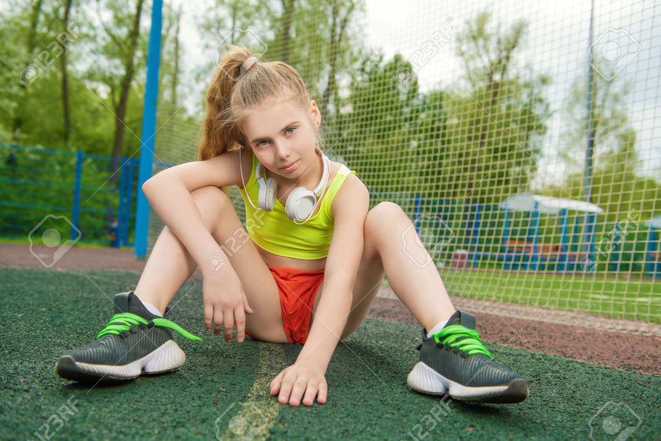 A full length portrait of a sporty teenager girl posing on the sports ground. Sport fashion, active lifestyle. - 127336993