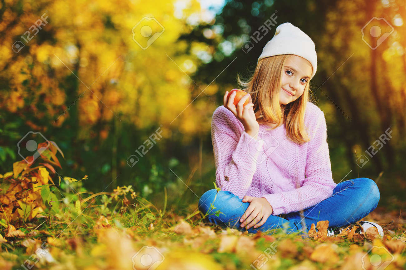 A pretty young girl is sitting on the ground with golden leaves and holding an apple. Autumn fashion, beauty. Healthy lifestyle. - 129199133