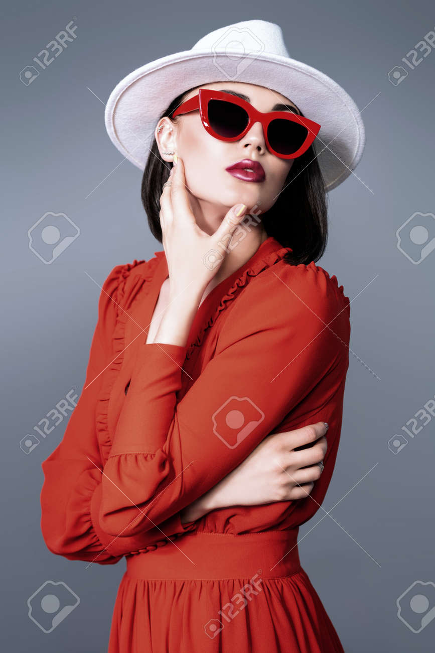 A portrait of a beautiful woman wearing a hat and sunglasses. Fashion, style, beauty, optics. - 129686521