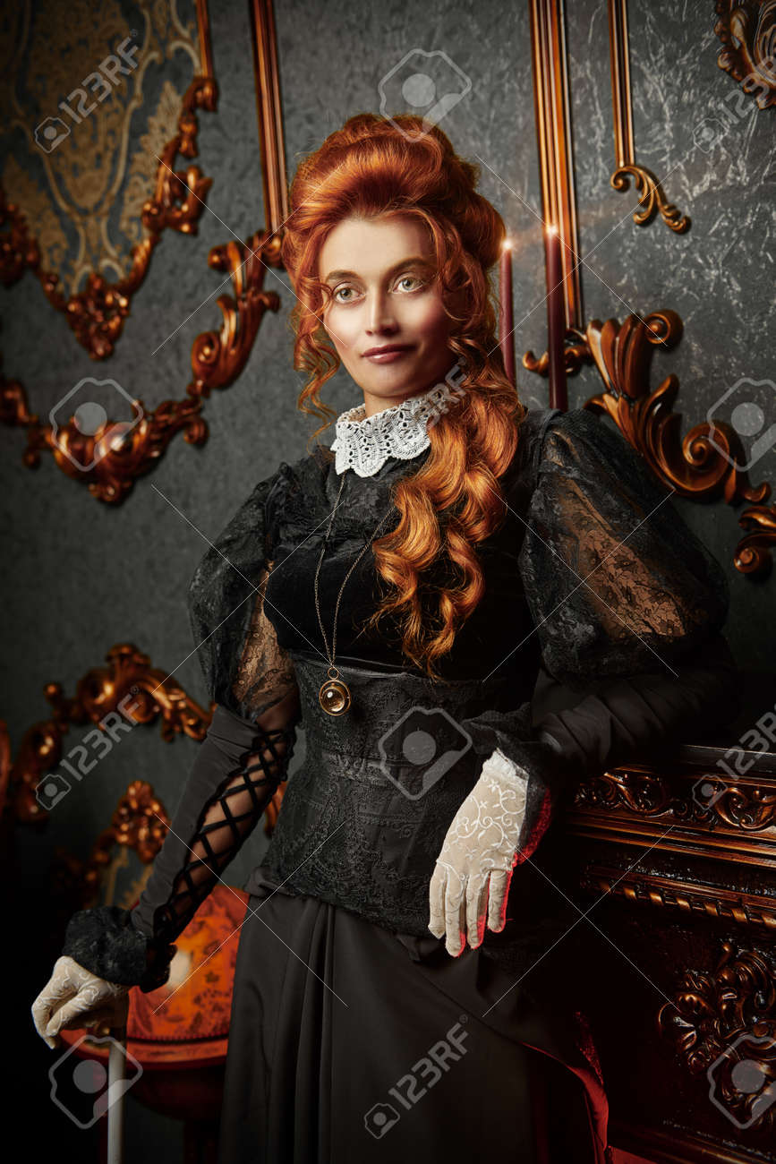 The Victorian era concept. Beautiful woman in elegant historical dress and hairstyle posing in vintage interior. Baroque. Fashion. - 130321418