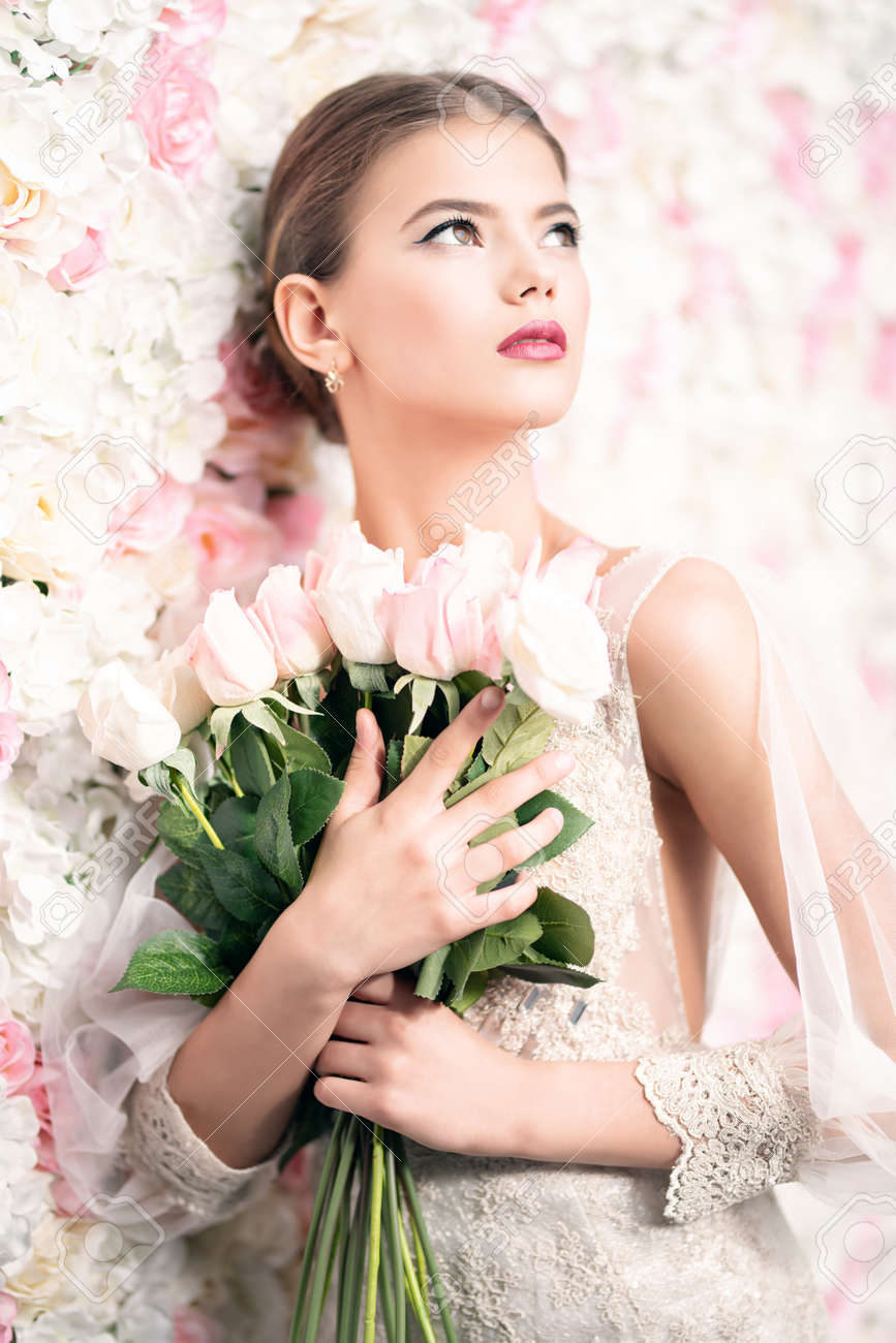 A portrait of a dreamy lady in a wedding dress posing indoor with flowers. Wedding, beauty, fashion. - 130843777
