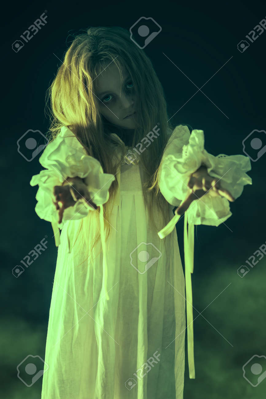 Scary little girl ghost in a white nightgown holds out her hands forward. Black background. Halloween. - 131537794