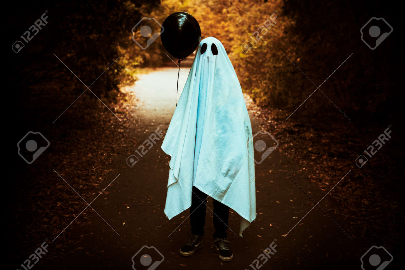 A lonely ghost of a child under a white sheet stands with a black balloon on a deserted road in the forest. Halloween. - 131448143
