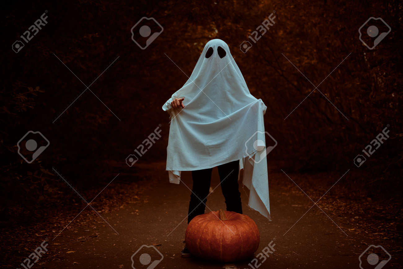 A ghost of a child under a white sheet stands in a shadow forest with pumpkin. Halloween concept. - 131448360