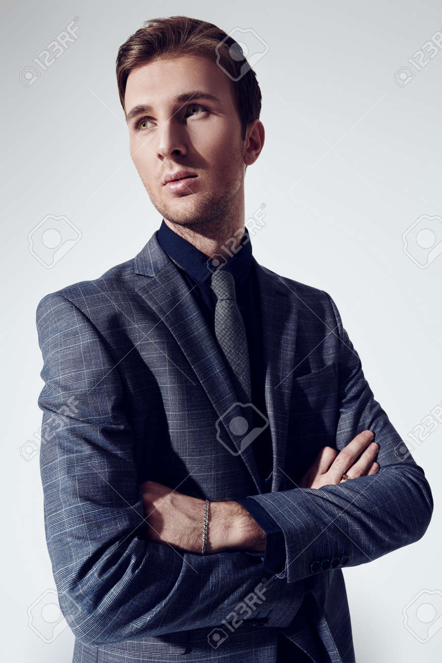 A portrait of a handsome young businessman in a formal suit at studio. Men's fashion. - 135950597
