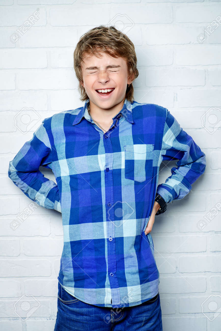 A portrait of a laughing teenager posing against a white wall. Education, knowledge. - 140977059