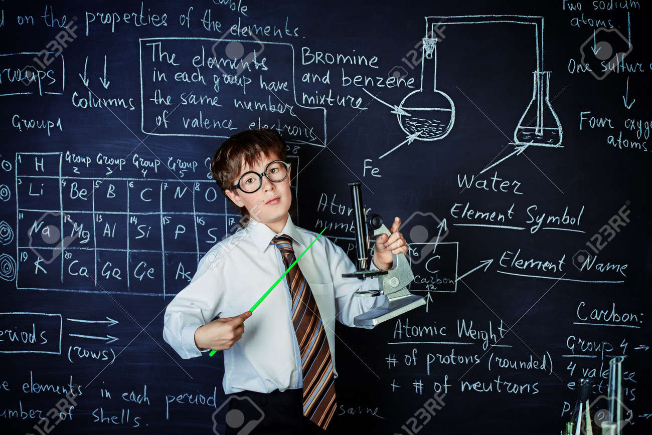 Serious schoolboy answering by a blackboard on a chemistry lesson. Educational concept. - 140958116