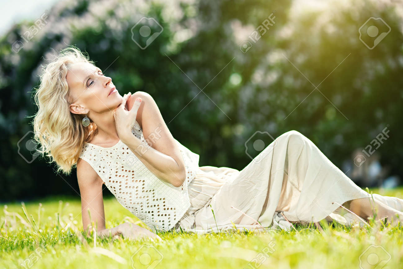 A portrait of an elderly woman relaxing on the grass in the summer park. Beauty, healthcare. - 142718849