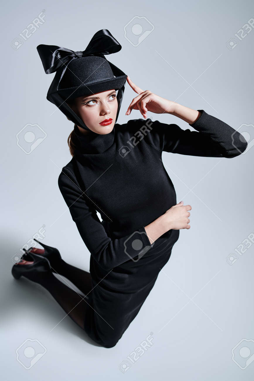 Fashion shot. Full length portrait of an elegant young woman in black fashionable hat and dress on a white background. Makeup and cosmetics. Copy space. - 144486901