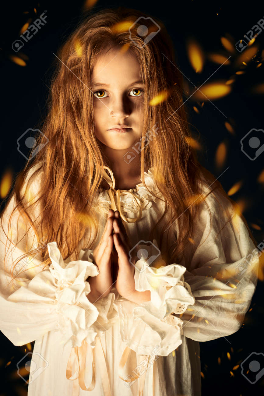 Scary little girl ghost in a white nightgown folded her hands in prayer. Black background. Halloween. - 145031630