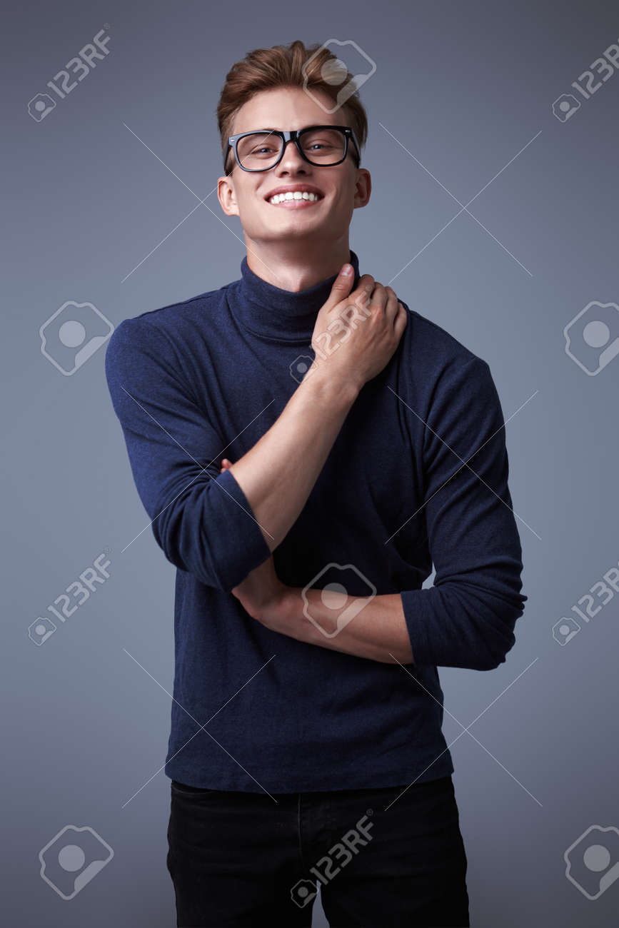 Male beauty. Portrait of a handsome young man with blond hair wearing glasses and smiling at camera. Optics for men. Copy space. - 149439483