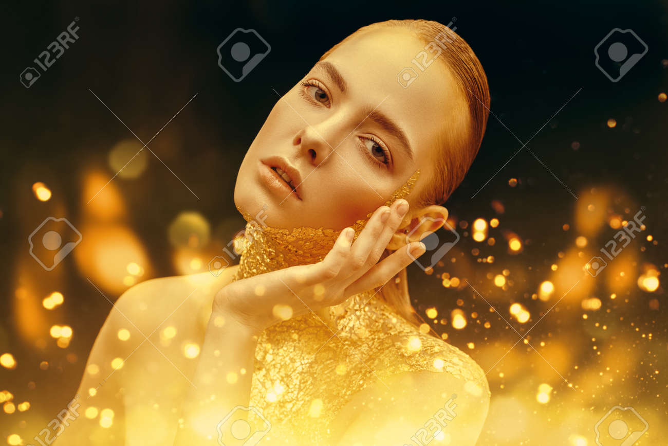 Beauty, fashion gold concept. Portrait of a beautiful girl model with golden skin and golden make-up on on a sparkling and black background with golden lights. Jewelry. Cosmetics and beauty care. - 150433037