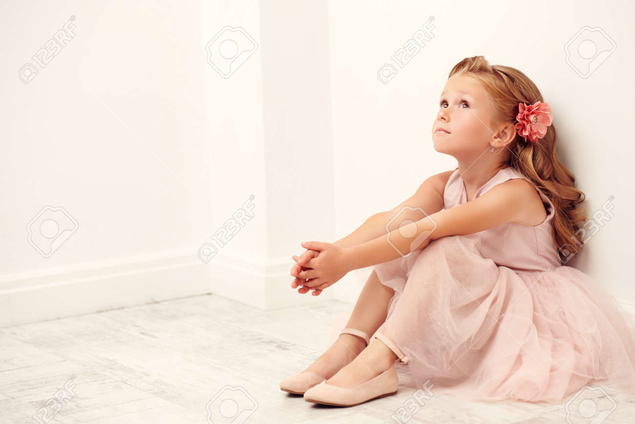 Portrait of a cute little girl sitting on the floor in a white room. Studio shot. Happy childhood. - 151736266