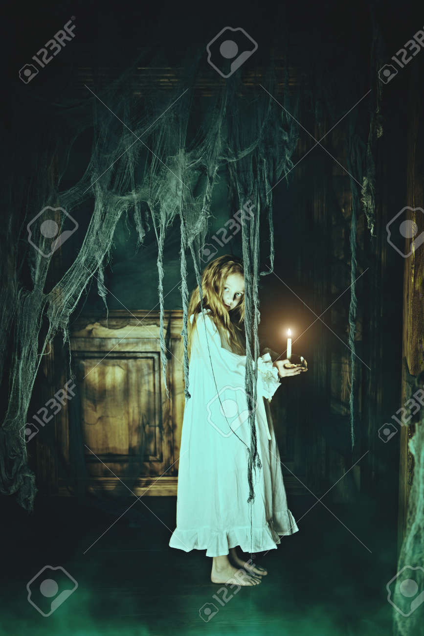 Halloween. A ghost girl in a nightgown wanders through the old house at night. - 152840783