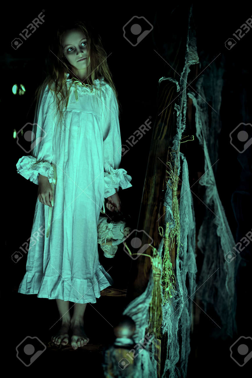 Scary little girl ghost in a white nightgown standing barefoot on the stairs and holds her doll and. Black background. Halloween. - 157098858