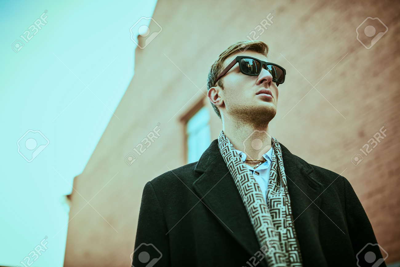 Urban men's style. Handsome man in black sunglasses and elegant black coat stands against the background of the grunge brick houses of the big city. - 158780097