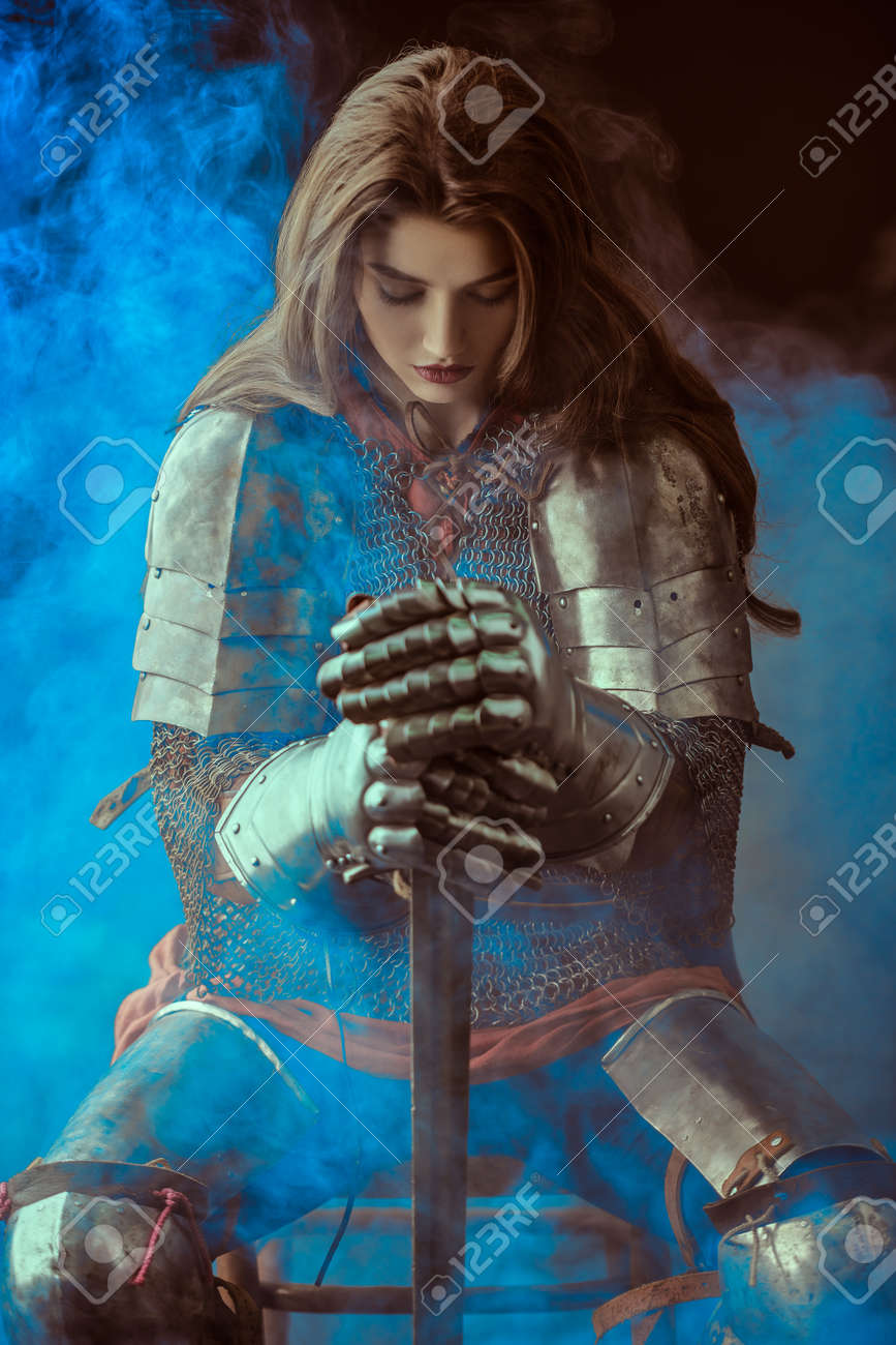 A beautiful noble warrior woman in chain mail and plate armor sits, leaning on her sword and bowing her head. Medieval knight. - 162393032