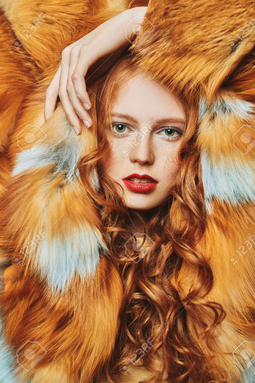 Fur coat fashion. Portrait of a beautiful young woman with long red hair posing in a luxurious fox fur coat. - 166409296
