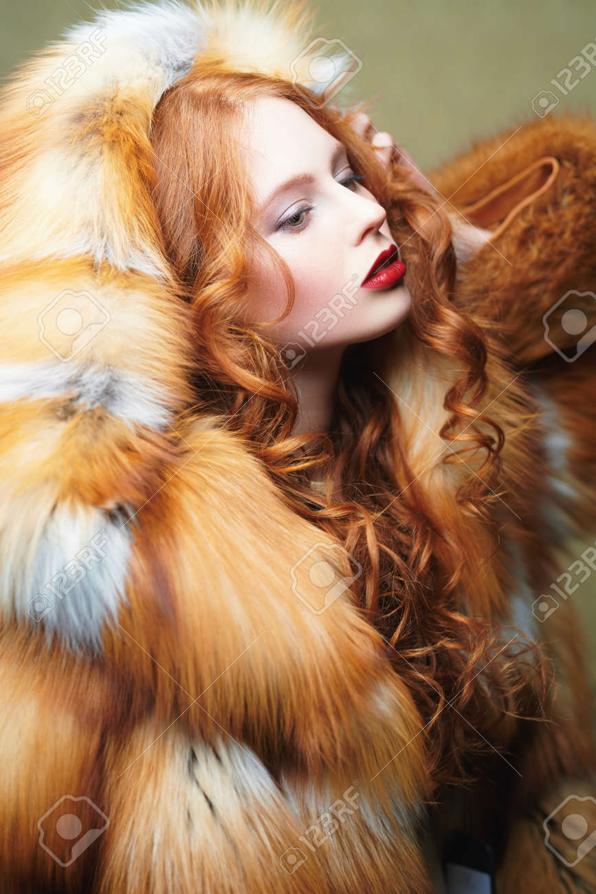 Portrait of a beautiful young woman with long red hair posing in a luxurious fox fur coat. Fur coat fashion. - 167519778