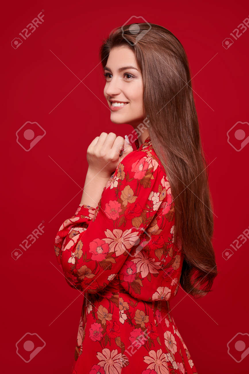 Charming happy girl in bright summer dress on a red background. Love and Valentine's Day. - 167921352
