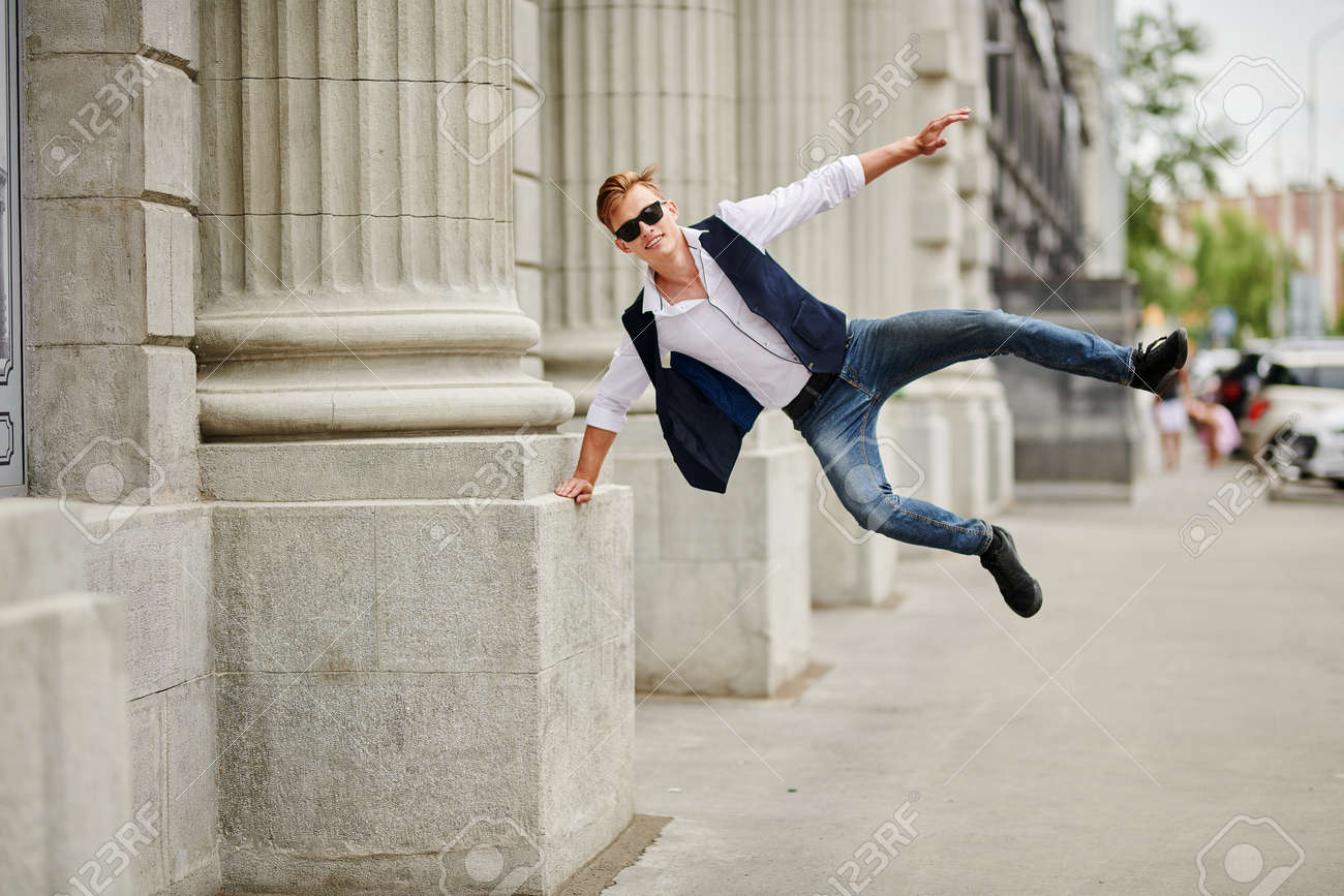 Handsome guy bounces with joy on the street. Summer fashion. Summer holidays and vacation. - 168321173