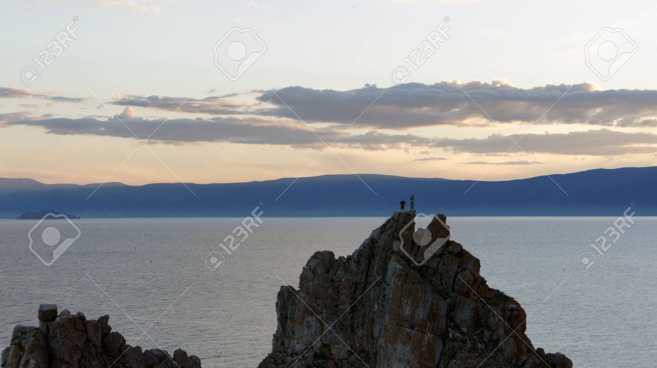 People at the top of the mountain. Beautiful sunset on the background Cape Burhan and Lake Baikal. - 50611535