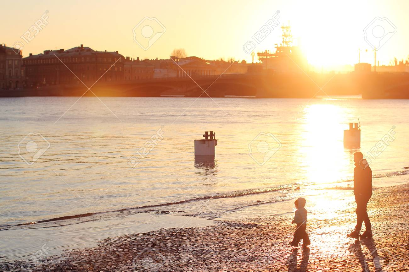 Dad with a child walking the city's waterfront. Spring evening in Saint Petersburg, the sunset on the Neva. - 55122816