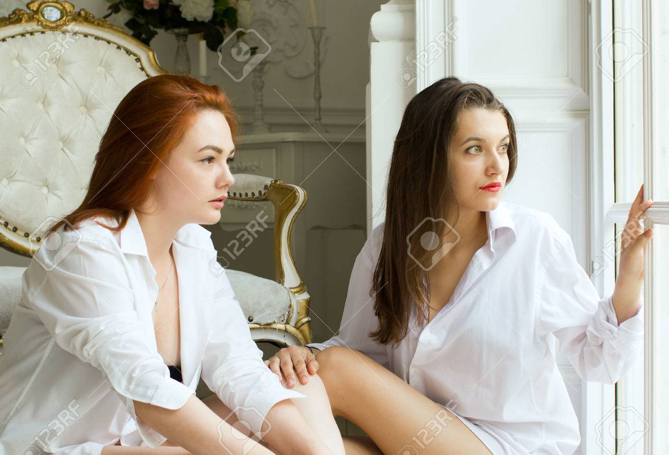 Two girls - a brunette and a redhead are sitting on the floor in a beautiful room. Amazingly beautiful girls in white shirts. - 78689755