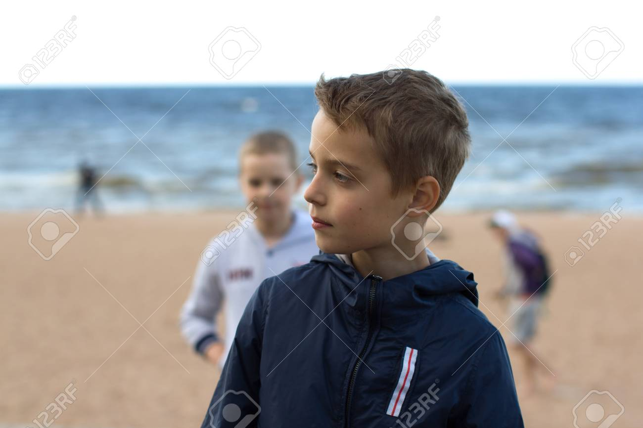Two teenage boys stand on the beach by the sea. Brothers walk along the seashore during the summer holidays. - 100832102