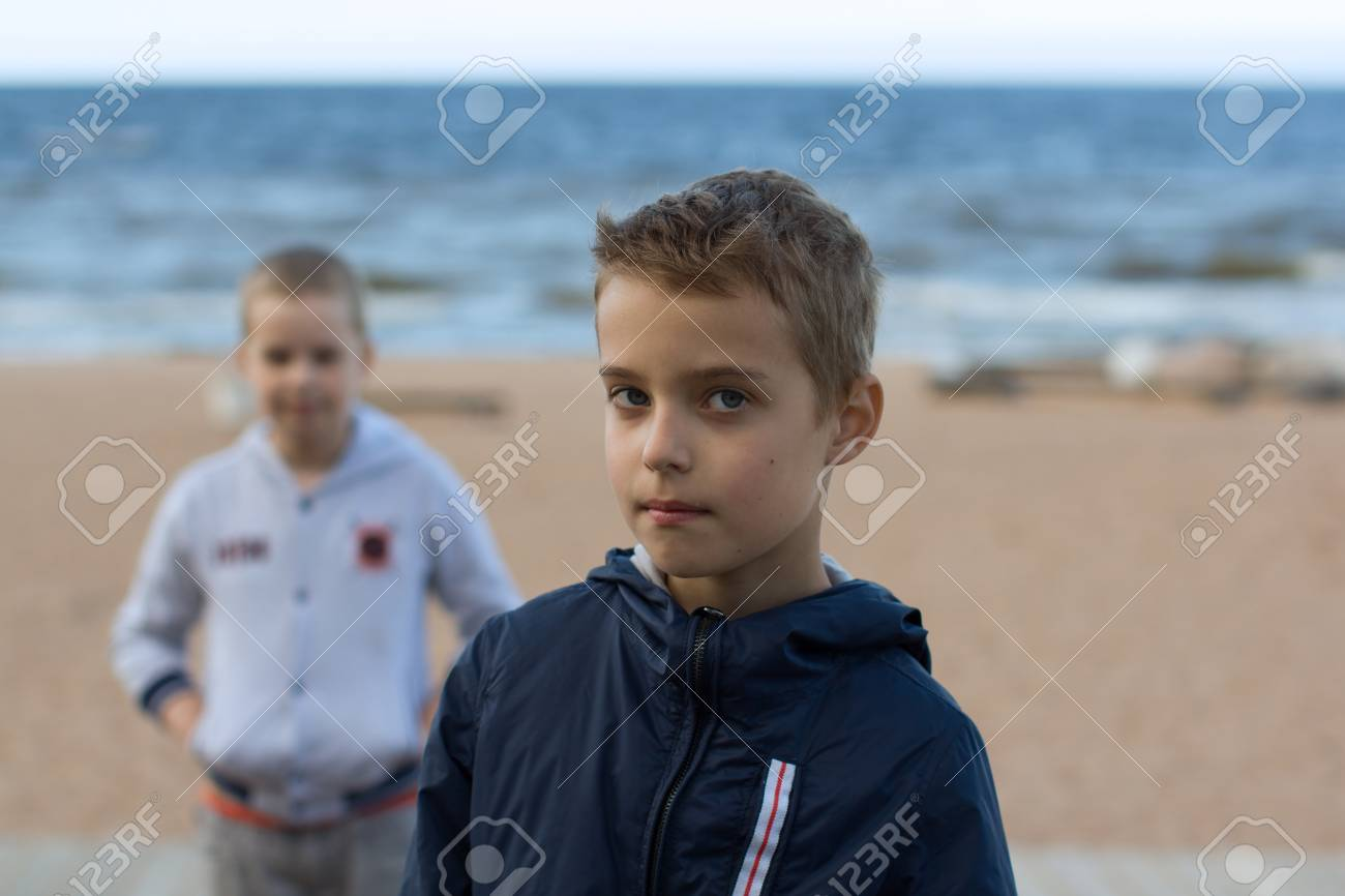 Two teenage boys stand on the beach by the sea. Brothers walk along the seashore during the summer holidays. - 100852863