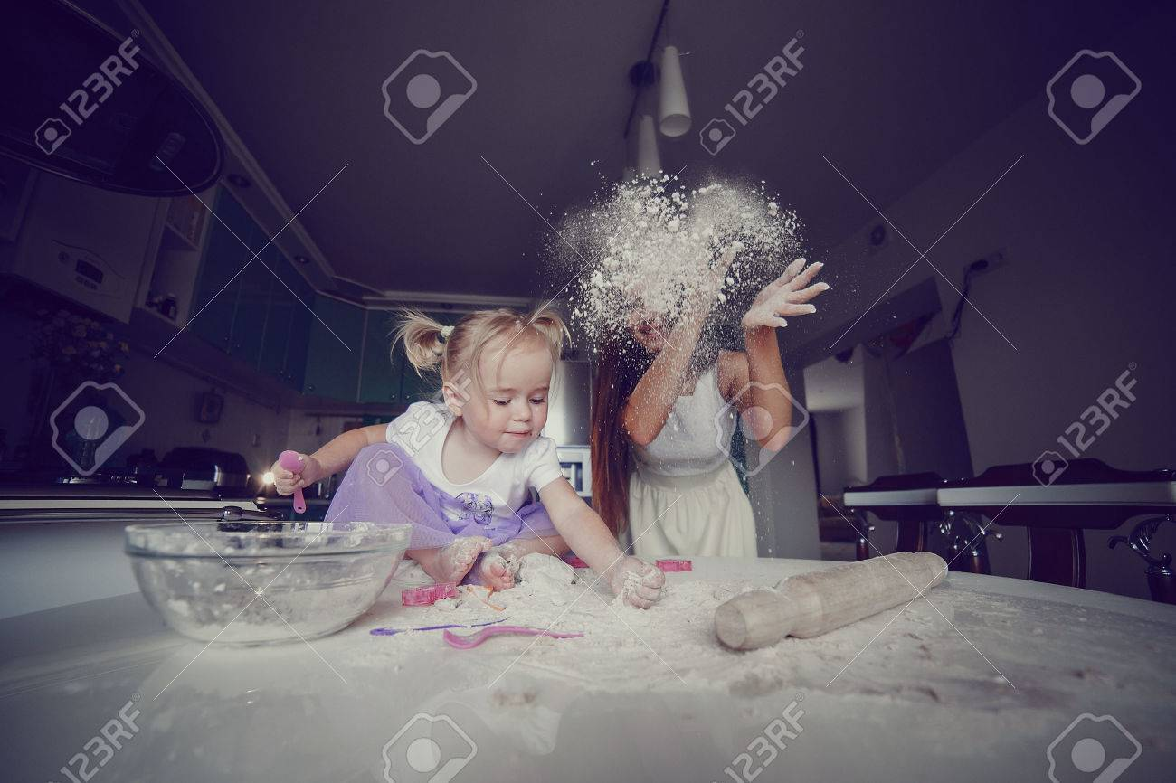 young beautiful mother teaches daughter prepare dough in the kitchen - 42926018