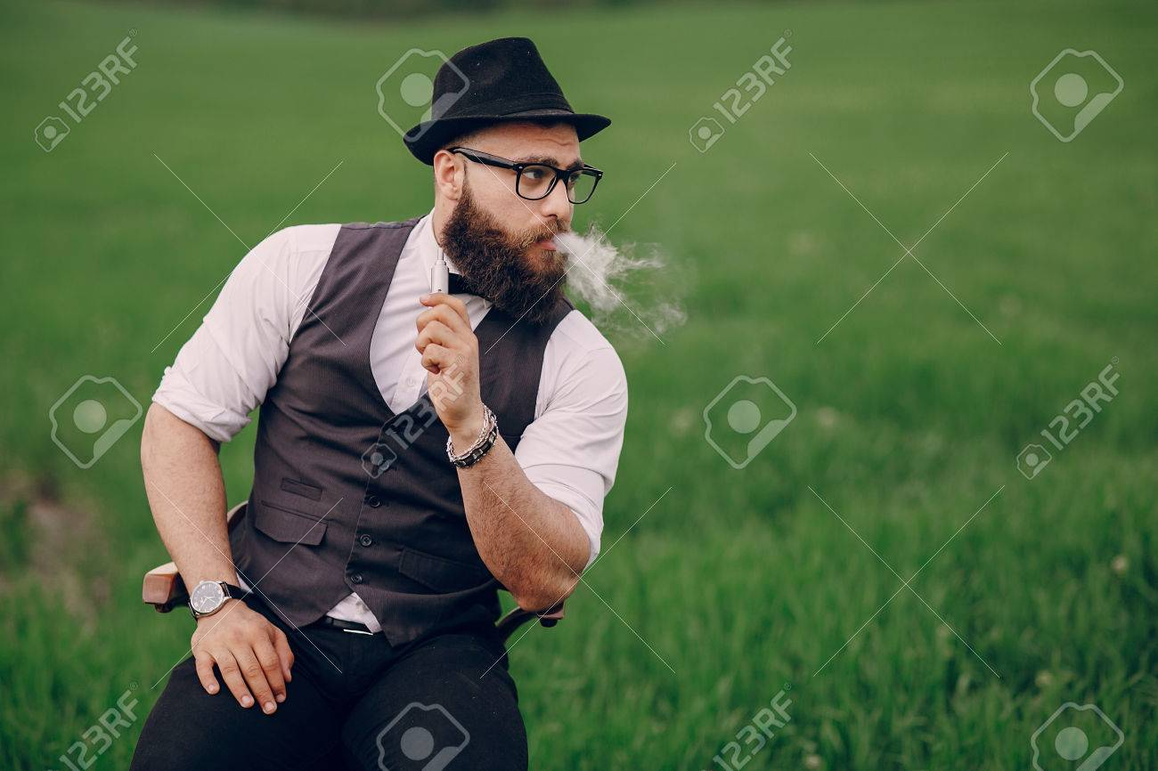 lone bearded man enjoys in the field of e-cigarette - 43876968