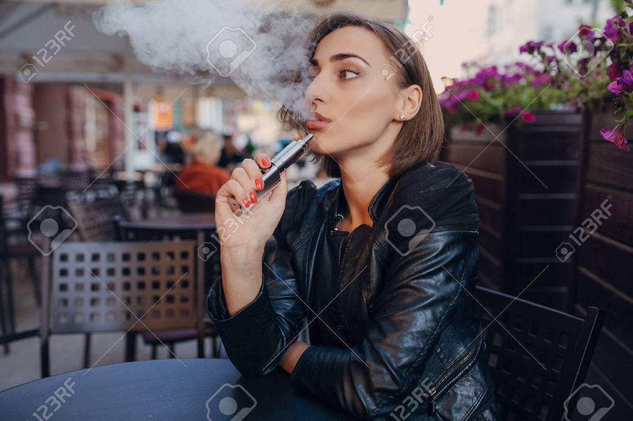 beautiful brunette woman in a cafe in a leather jacket - 45710653