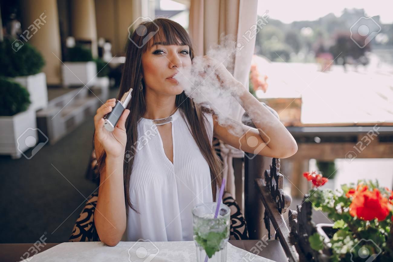 beautiful brunette smoke electronic cigarette on the summer terrace of restaurant - 47460739