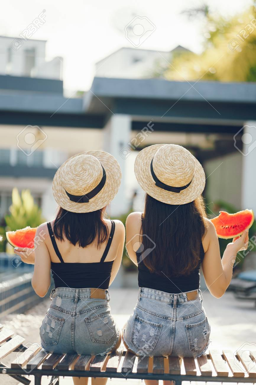 two girls eating watermelon - 103583785