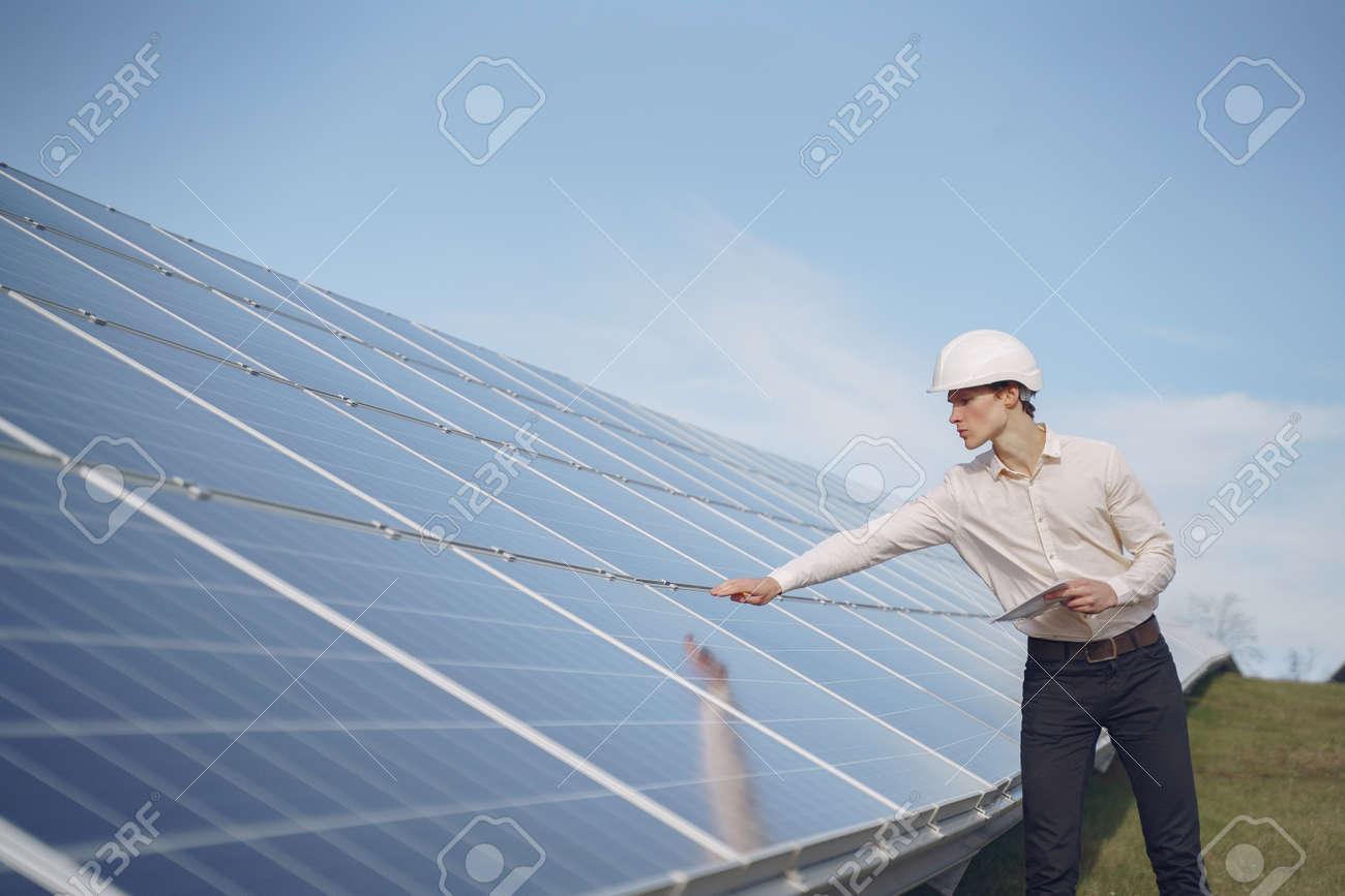Businessman in a white helmet near solar battery - 152517047