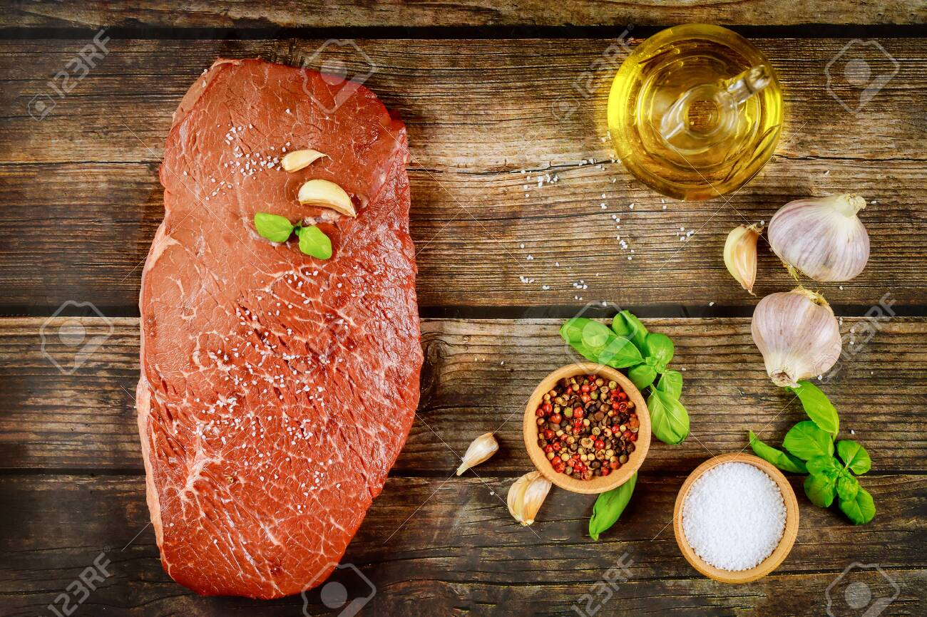 Raw beef meat on a wooden background with spice and oil. Top view. - 154412717