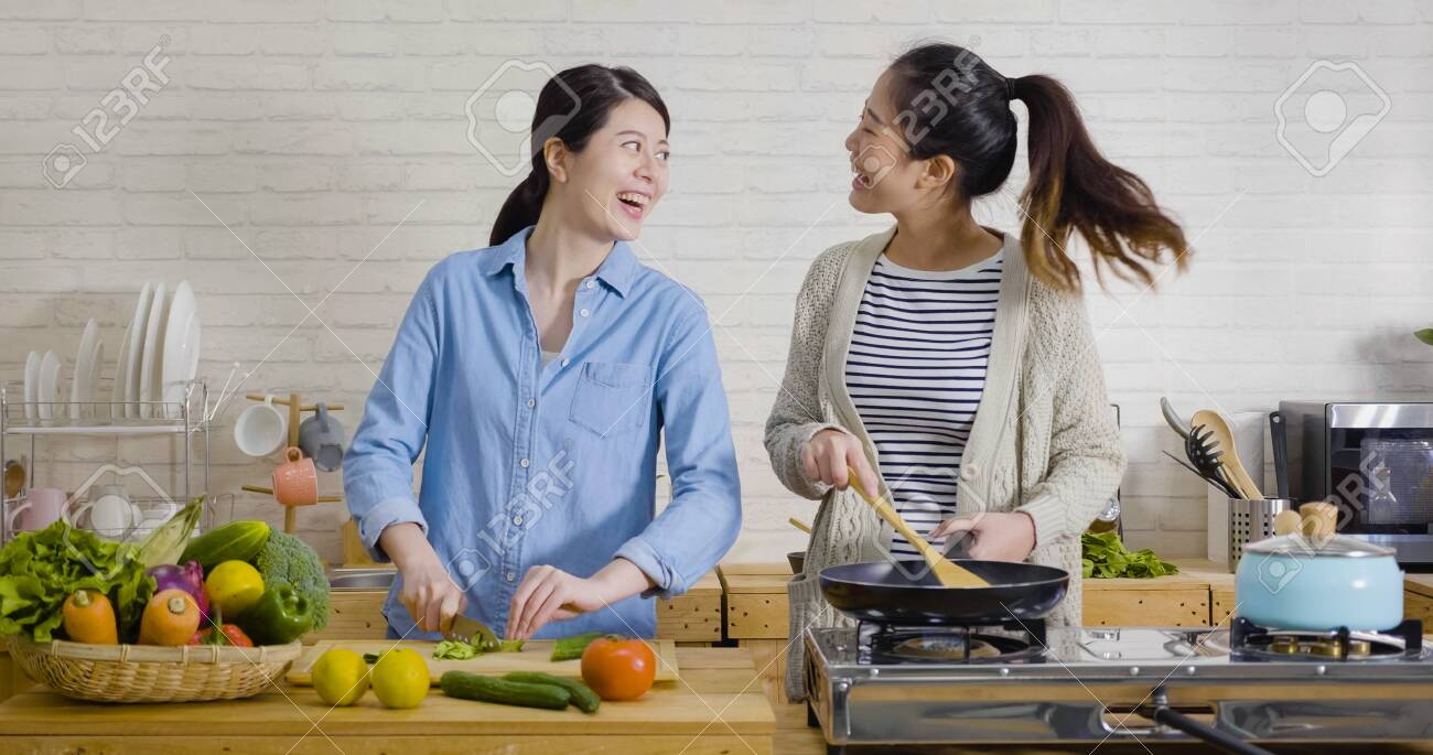 Young Female Friends In Kitchen Cooking Together Vegetarian Meal Stock Photo Picture And Royalty Free Image Image 143659689