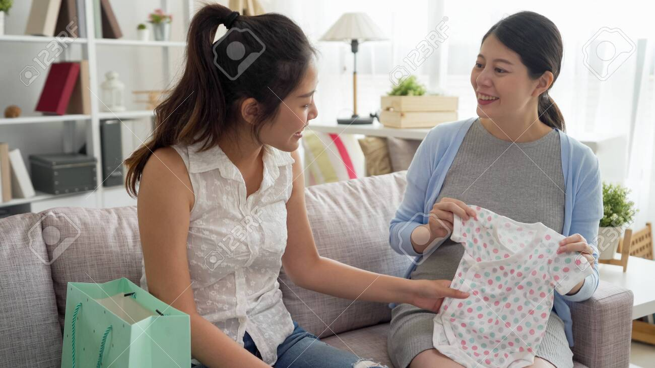 young asian korean girl sending gift of cute child clothes to maternity lady while celebrating baby shower in bright living room. - 157947511