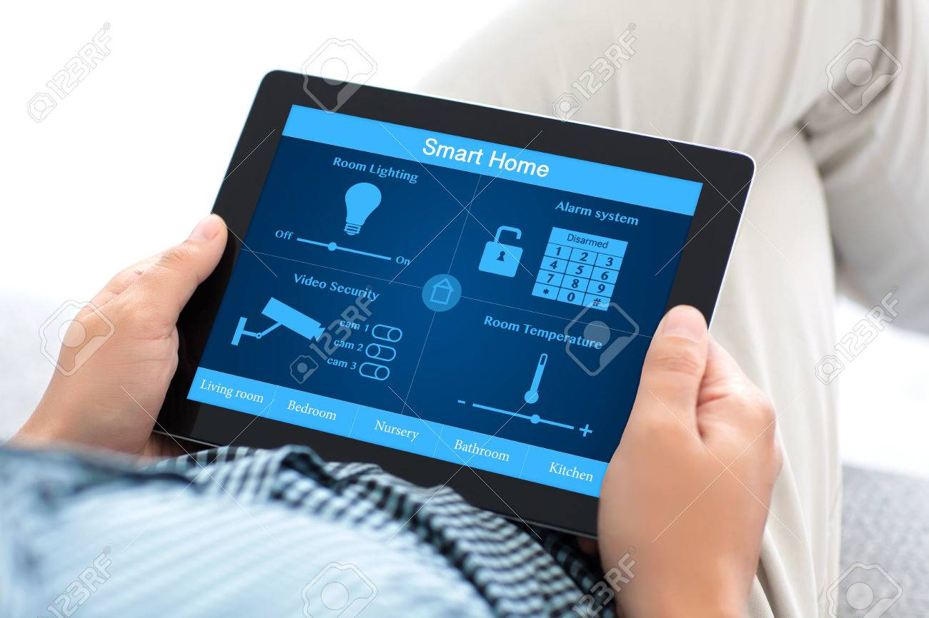 man sitting on a sofa and holding a tablet computer with smart home on the screen Stock Photo - 53553969