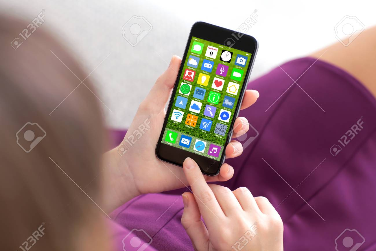 woman in purple dress holding touch phone with home screen icons