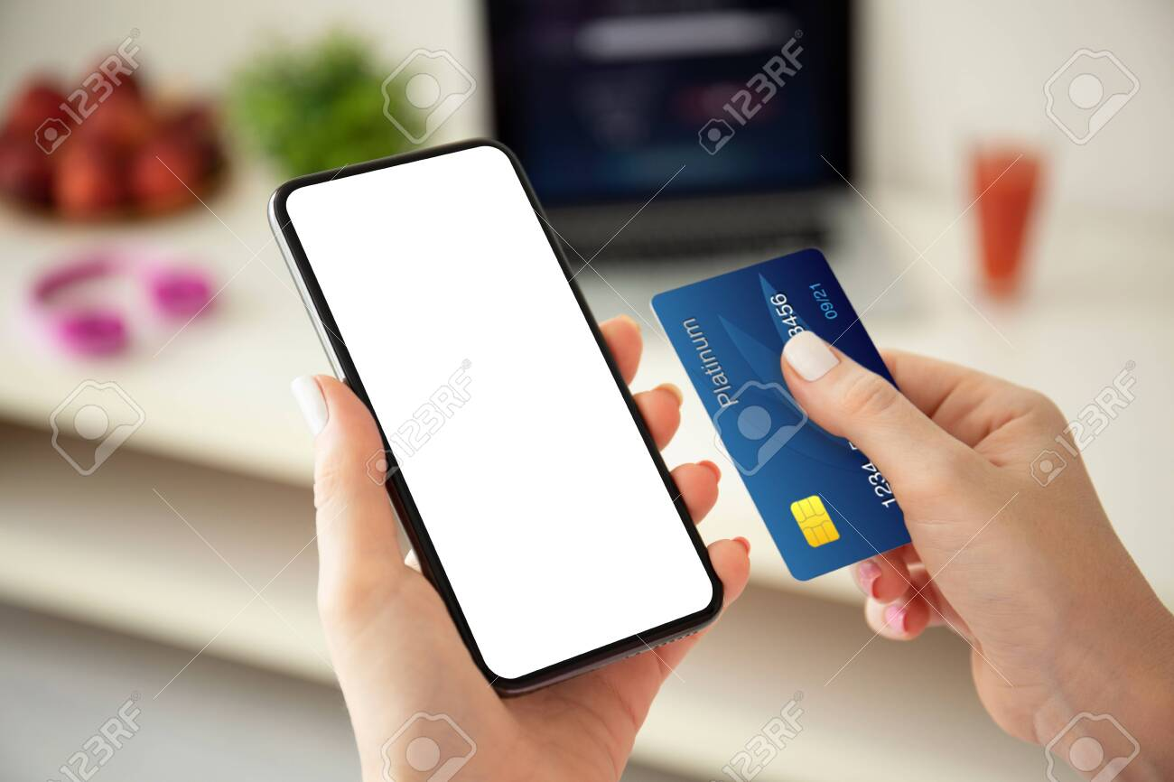 female hands holding phone with isolated screen and credit card on the background room - 137880322