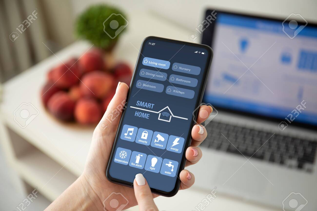 female hands holding phone with app smart home on the screen over a table with laptop in room - 142175396